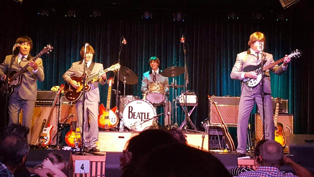 Australia's own Beatle Tribute band performing live on stage.