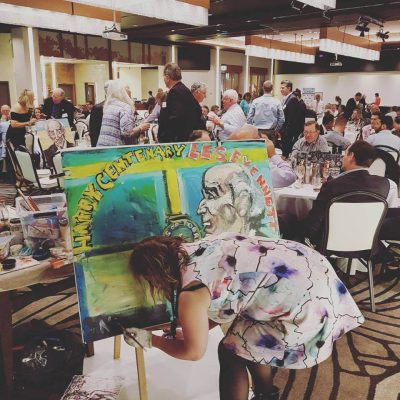 Sophie Downey paints Les Evennett's portrait during the course of the luncheon as the live entertainment offering of the day