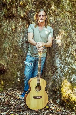 Singer Songwriter Glen Mead poses with an acoustic guitar. - All Things Entertainment